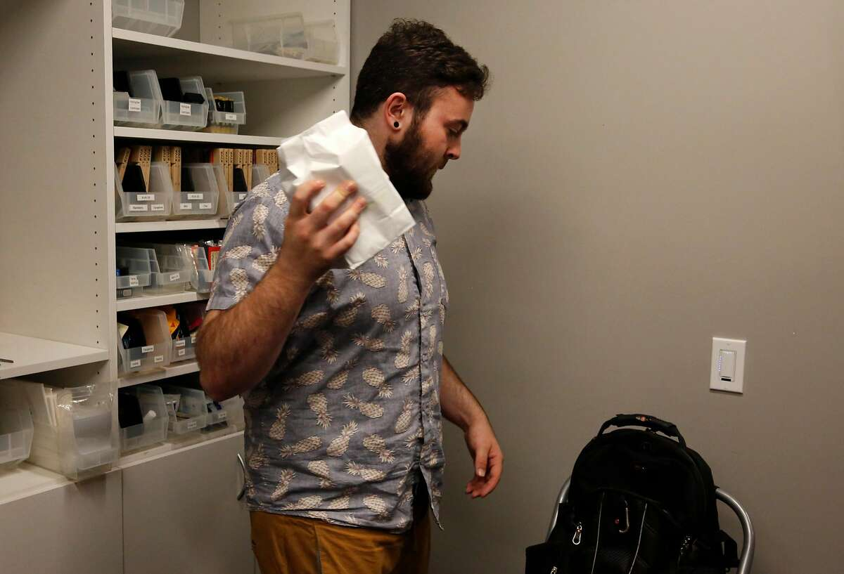 JP Noda, a delivery person for The Apothecarium, puts an order into his bag before leaving to deliver multiple orders to clients August 10, 2017 in San Francisco, Calif.