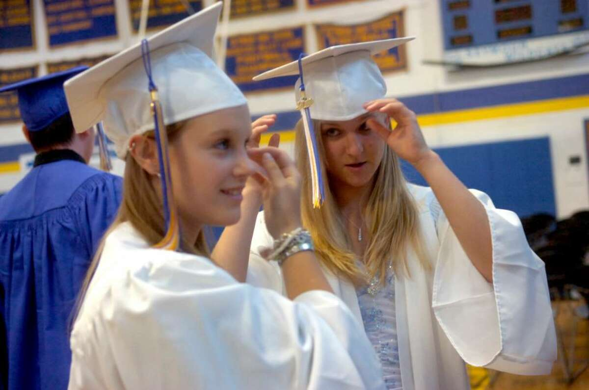 Amber Stevens, left, and Jessica Spooner, right, both 17, adjust their caps before Seymour High School's graduation ceremony Wednesday, June 16, 2010.