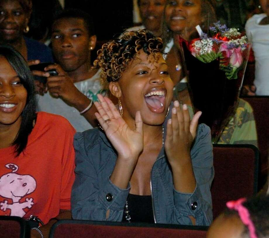 Antquanette Chisolm cheers as her graduating sisters, Alexis and Alexandra, enter the auditorium, during Bridge Academy's 13th Annual Commencement Exercises held at Thurgood Marshall Middle School in Bridgeport, Conn. on Wednesday evening June 16, 2010. Photo: Christian Abraham / Connecticut Post