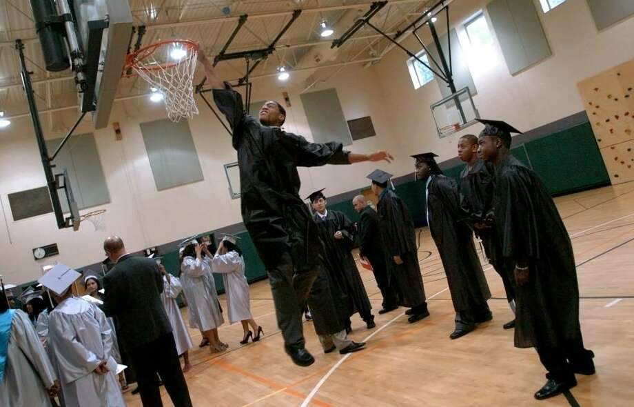 Graduate Christian Bish slam dunks a badminton birdie he found in the gym while getting ready, before the start of Bridge Academy's 13th Annual Commencement Exercises held at Thurgood Marshall Middle School in Bridgeport, Conn. on Wednesday evening June 16, 2010. Photo: Christian Abraham / Connecticut Post