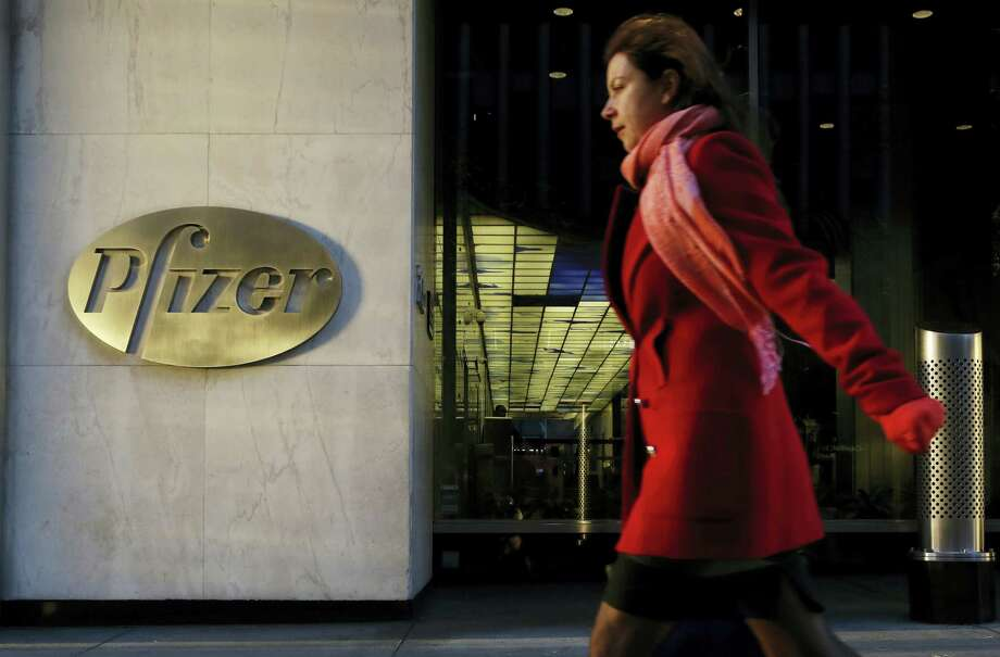 A woman passes Pfizer's world headquarters, in New York. Pfizer Inc. (PFE) on Tuesday, Jan. 31, 2017, reported fourth-quarter net income of $775 million, after reporting a loss in the same period a year earlier. Photo: AP Photo/Mark Lennihan, File  / Copyright 2016 The Associated Press. All rights reserved.