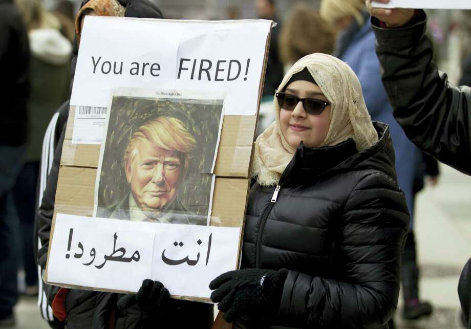 A woman carries a sign outside of the White House during a demonstration to denounce President Donald Trump's executive order that bars citizens of seven predominantly Muslim-majority countries from entering the United States on Sunday in Washington. Photo: Jose Luis Magana — The Associated Press  / FR159526 AP