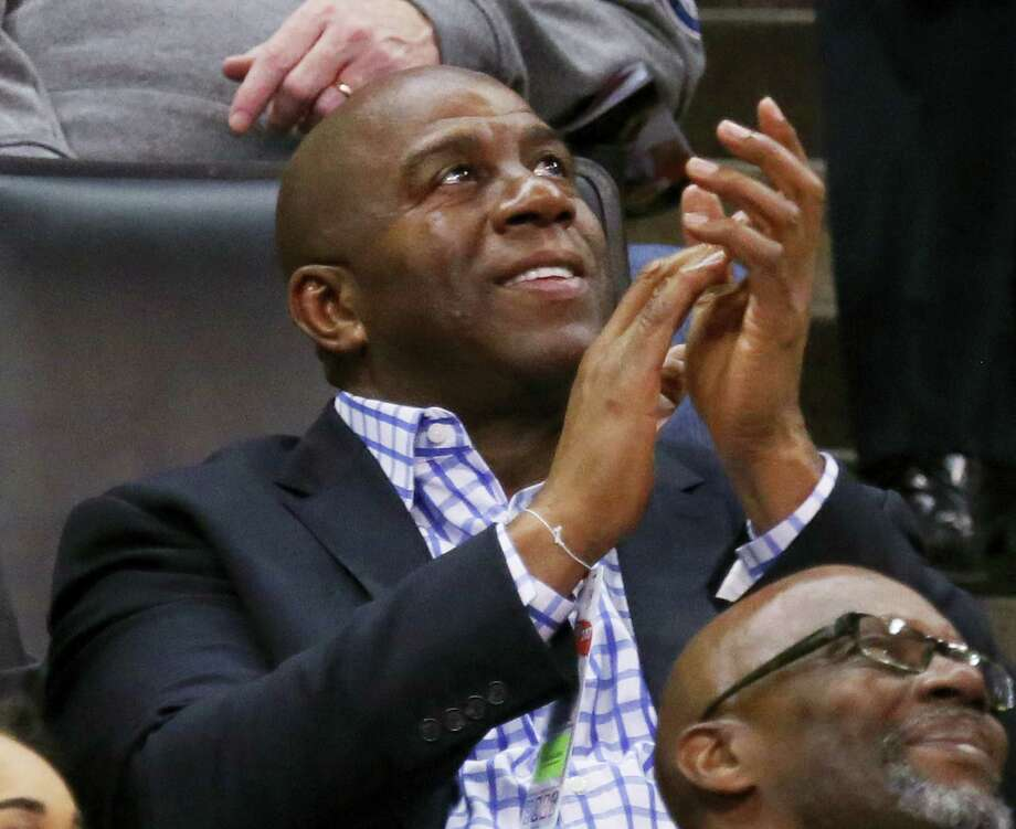 Magic Johnson, president of basketball operations for the Los Angeles Lakers, applauds as he watches the kiss cam on the scoreboard during the third quarter of an NBA basketball game between the Lakers and the Oklahoma City Thunder in Oklahoma City on Feb. 24, 2017. Oklahoma City won 110-93. Photo: AP Photo — Sue Ogrocki  / AP2017