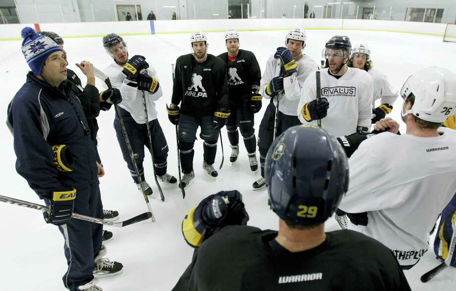 Former Buffalo Sabres player Andrew Peters, left, and Sabres players talk during a workout. Photo: The Associated Press File Photo  / AP2013