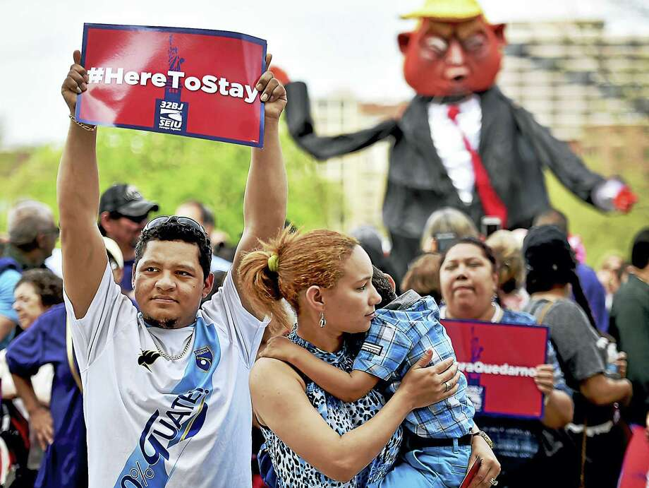 """Norwalk residents Alexander Cruz, 28, emigrated from Guatemala and his wife, Yeidy Cruz, came to the United States from the Dominican Republic who is holding their 4-year old son Dylan who has his eye on the giant-sized Donald Trump puppet at the """"Here to Stay"""" immigrant rights rally, Saturday, where hundreds of residents from across Connecticut gather at the State Capitol in Hartford. Photo: Catherine Avalone — New Haven Register  / Catherine Avalone/New Haven Register"""