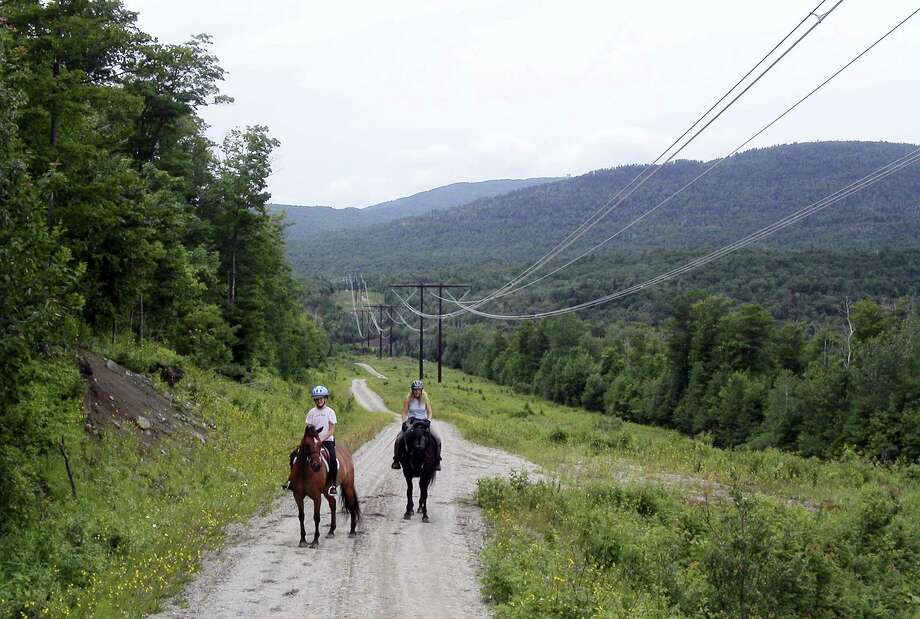 In this undated photo two people ride horses along power lines owned by the Vermont Electric Power Company where they run through wildlife areas in Ferdinand, VT. National Grid has proposed construction of new electric transmission lines alongside these existing lines that would carry Canadian power through northeastern Vermont to southern New England reopening the long-settled conservation easements governing the use of the land the new lines would traverse. Photo: AP Photo — Wilson Ring  / Copyright 2017 The Associated Press. All rights reserved.