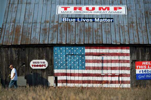 "Small business owner Jason Scaggs, age 36, touches up one of the many painted sentiments on his ""Flag Barn"" in Owings, Maryland, on November 2, 2016. Like many voters, Scaggs is fed up with career politicians in Washington."