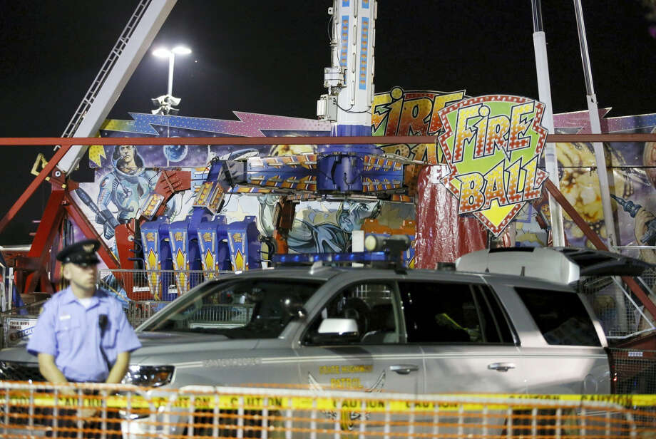 Authorities stand near the Fire Ball amusement ride after the ride malfunctioned injuring several at the Ohio State Fair, Wednesday, July 26, 2017, in Columbus, Ohio. Some of the victims were thrown from the ride when it malfunctioned Wednesday night, said Columbus Fire Battalion Chief Steve Martin. (Barbara J. Perenic/The Columbus Dispatch via AP) Photo: AP / 2017 The Columbus Dispatch