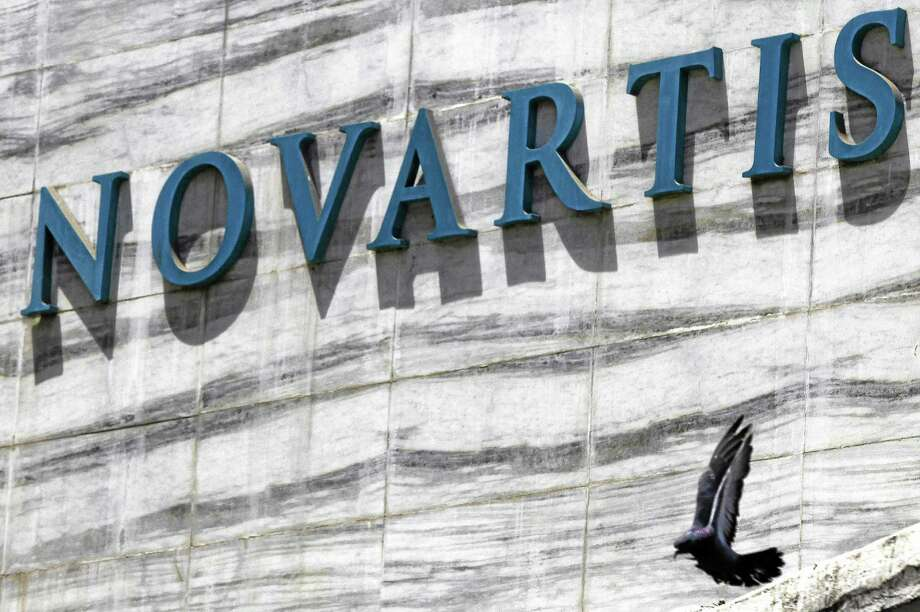 A dove flies near the logo of Novartis India Limited at their head office in Mumbai, India on April 1, 2013. India's Supreme Court on Monday rejected drug maker Novartis AG's attempt to patent a new version of a cancer drug Glivec, in a landmark decision that healthcare activists say ensures poor patients around the world will get continued access to cheap versions of lifesaving medicines. Photo: AP Photo — Rafiq Maqbool  / AP