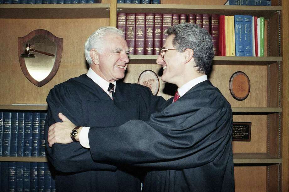 """In this Oct. 13, 1989 photo, retired Judge Joseph A. Wapner of TV's 'The People's Court' congratulates his son, Judge Frederick N. Wapner, right, as he was enrobed as a Municipal Court judge in Los Angeles. Wapner, who presided over """"The People's Court"""" with steady force during the heyday of the reality courtroom show, has died. Wapner died at home in his sleep on Feb. 26, 2017, according to his son, David Wapner. Photo: AP Photo/Nick Ut, File  / Copyright 2017 The Associated Press. All rights reserved."""