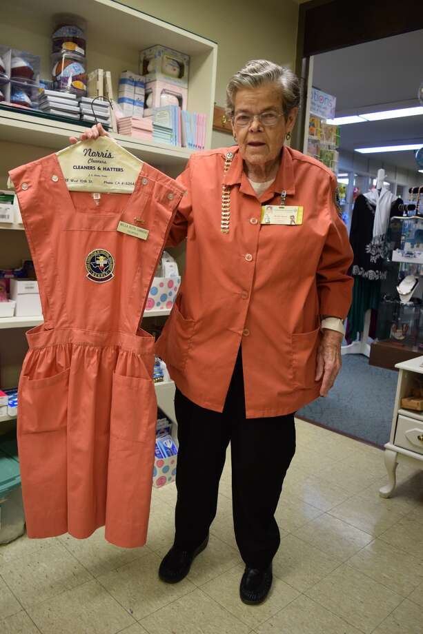 Longtime Hospital Auxiliary member Willa Ruth Simmons displays an old Pink Lady's uniform while wearing her more modern smock. She has volunteered at the hospital for almost 50 years.