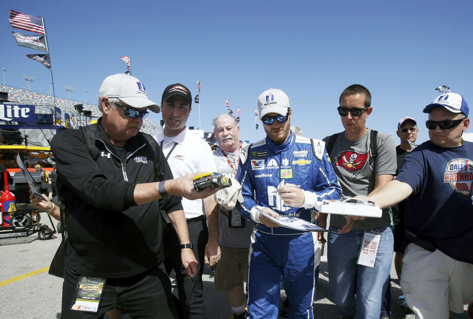 Dale Earnhardt Jr., center, signs autographs for fans at a practice session at Daytona International Speedway on Friday. Photo: John Raoux — The Associated Press  / Copyright 2017 The Associated Press. All rights reserved.