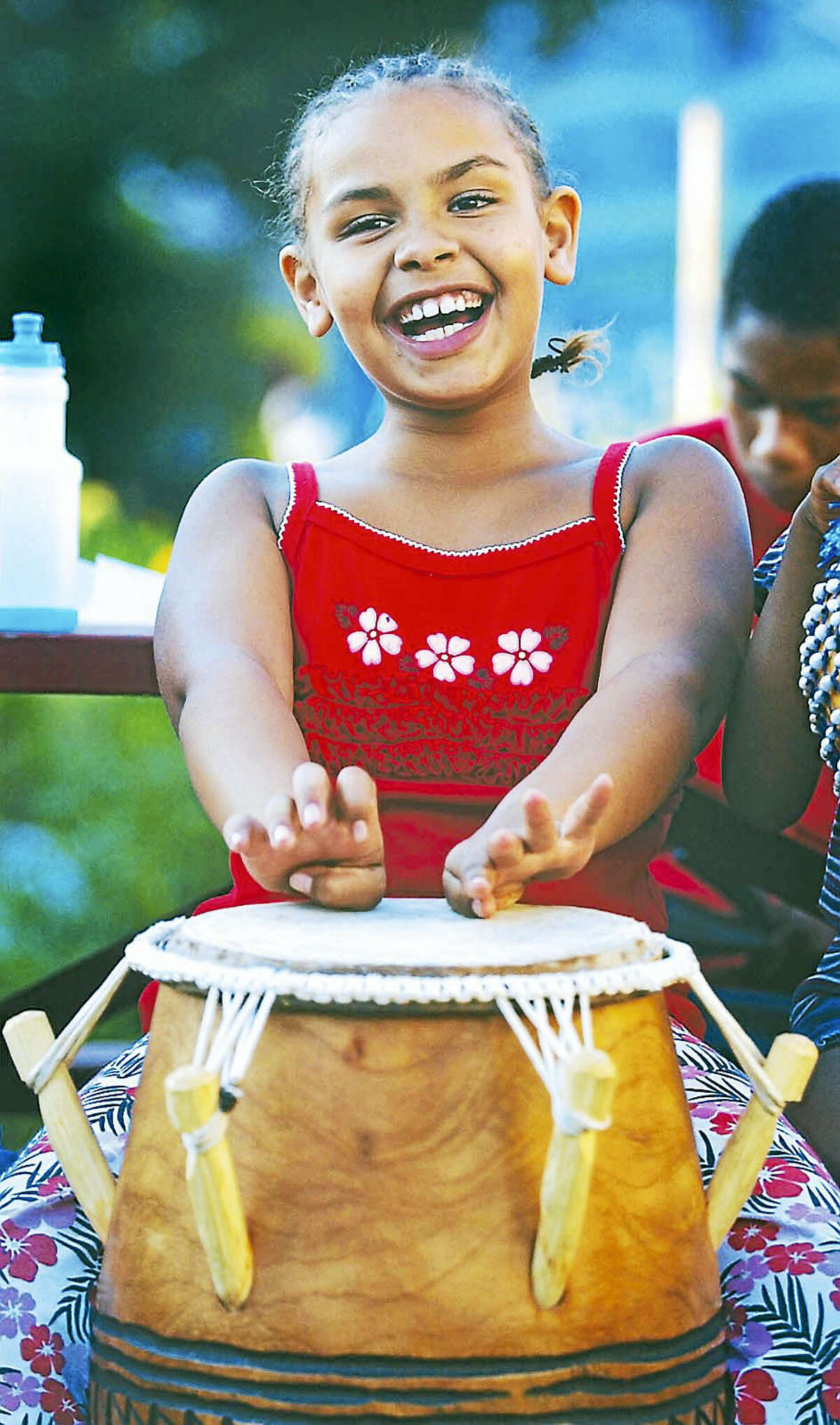 Kayla Daley laughs while drumming on an Oprenten hand drum from the West African nation of Ghana in the Ferry Street Community Garden at the Green Street Arts Center in this file photo.