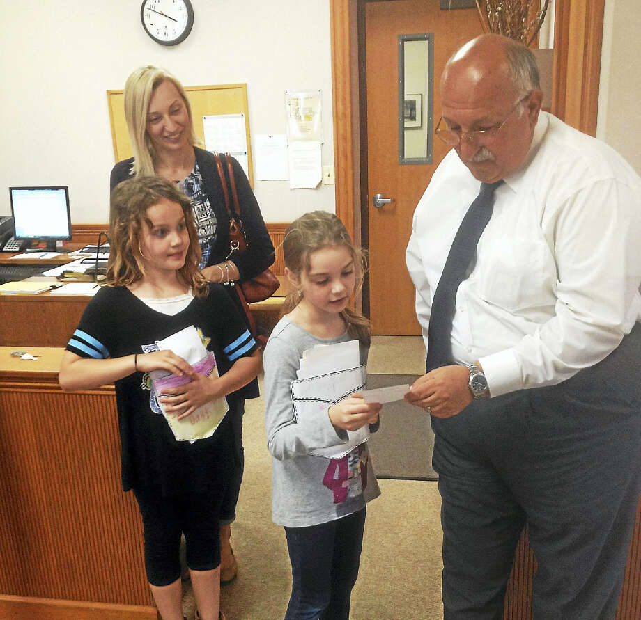 From left are Cromwell Edna C. Stevens Elementary School second-grade students Nyla and Sara presenting their poems to Town Manager Anthony J. Salvatore. At the back is chaperone Karolina Lipka. Photo: Jeff Mill — The Middletown Press