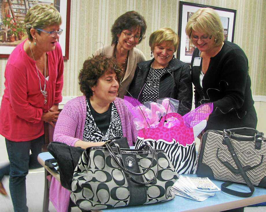 Members of the Middlesex United Way Women's Initiative review a list of silent auction items for a Power of the Purse fundraiser in this archive photograph. Photo: File Photo