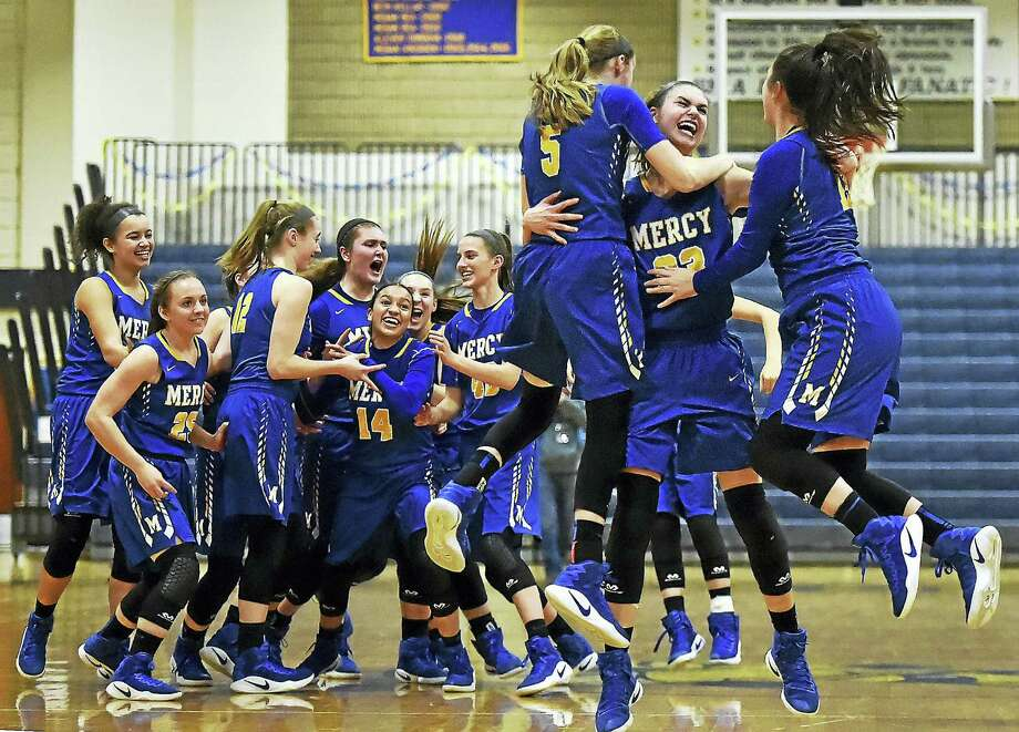 Mercy junior guard Isabella Santoro (5) and senior guard Tia Giansiracusa (13) join Mercy junior forward Samantha Chapps (23) in a victory celebration after the Tigers defeated Hand 49-39 in the SCC championship game Wednesday at East Haven High School. Photo: Catherine Avalone — New Haven Register  / Catherine Avalone/New Haven Register