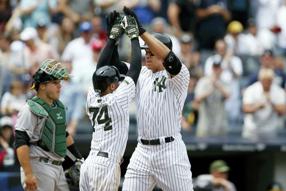 Aaron Judge, right, celebrates after his third-inning grand slam on Sunday. Photo: Kathy Willens — The Associated Press  / Copyright 2017 The Associated Press. All rights reserved.