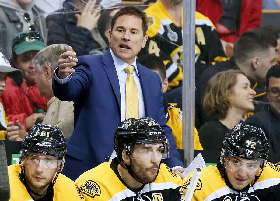In this file photo, Boston Bruins interim head coach Bruce Cassidy works behind the bench in the third period of an NHL hockey game against the Washington Capitals. The Bruins said on Wednesday it will drop the interim tag and Cassidy will return next season as the team's head coach. Cassidy replaced Claude Julien in February and helped the team return to the playoffs for the first time in three seasons. Photo: Winslow Townson — The Associated Press File  / FR170221 AP
