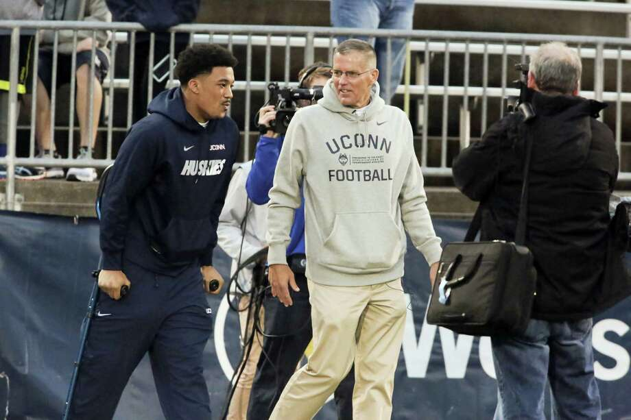 Injured player E.J. Levenberry talks with UConn football coach Randy Edsall before the NCAA college football team's spring game last Friday at rentschler Field. Edsall is looking forward to playing Boston College at Fenway Park in November in what is considered one of the Huskies' home games. Photo: Michael McAndrews — Hartford Courant Via AP  / Hartford Courant