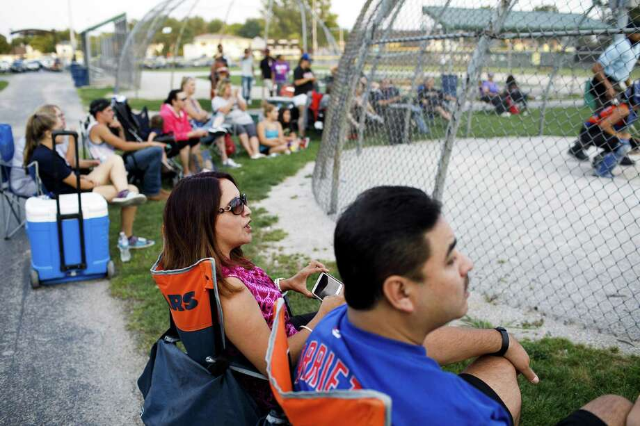From left, Marilu Arce and her husband Raul Arce watch their daughter Alyssa Arce, 17, play softball at Bettenhausen Park on Tuesday, Aug. 1, 2017 in Tinley Park, Ill. Marilu Arce, an assistant controller in the corporate accounting department at the Chicago-based National Equity Fund, works from her Mokena home two days a week and says dropping her commute has given her time to take her daughters to after-school activities. Photo: Armando L. Sanchez /TNS / Chicago Tribune