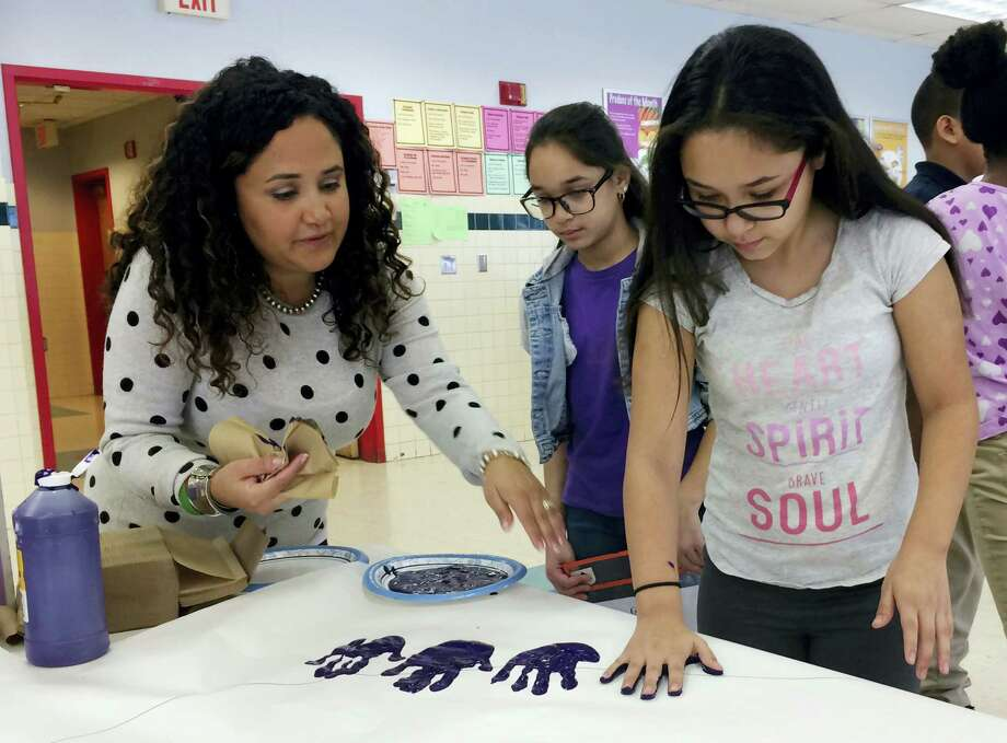 In this Feb. 14, 2017 photo, Nelba Marquez-Greene helps 10-year-old Araceli Buchko put her hand print inside a giant paper heart as part of the Love Win's campaign's Friendship Day, a social and emotional learning activity at the Chamberlain Elementary School in New Britain, Conn. Photo: AP Photo/Pat Eaton-Robb  / Copyright 2017 The Associated Press. All rights reserved.