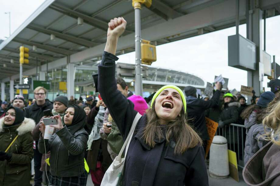 A protester raises her fist and shouts as she joins others assembled at John F. Kennedy International Airport in New York on Saturday after two Iraqi refugees were detained while trying to enter the country. On Friday, Jan. 27, President Donald Trump signed an executive order suspending all immigration from countries with terrorism concerns for 90 days. Countries included in the ban are Iraq, Syria, Iran, Sudan, Libya, Somalia and Yemen, which are all Muslim-majority nations. Photo: Craig Ruttle — AP Photo / FR61802 AP
