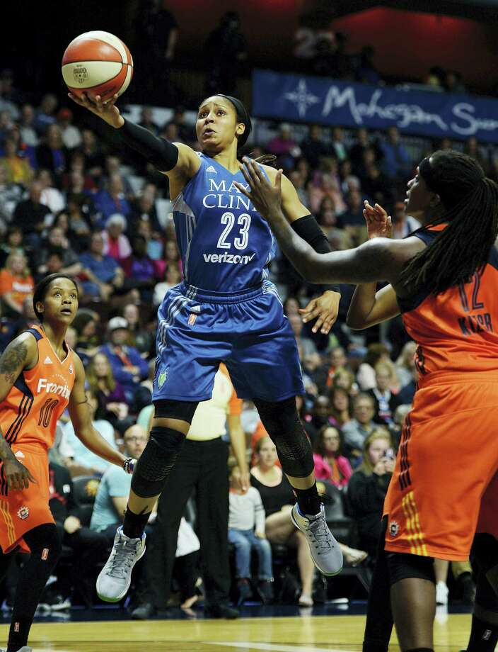 The Lynx's Maya Moore drives to the basket between the Sun's Jasmine Thomas, left, and Lynetta Kizer in the first half Friday. Photo: Sean D. Elliot — The Day Via AP  / 2017 The Day Publishing Company