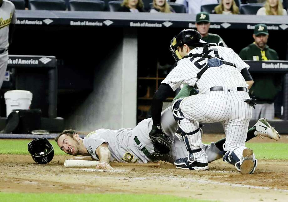 Yankees catcher Austin Romine, right, tags out the Athletics' Adam Rosales in the eighth inning Friday. Photo: Frank Franklin II — The Associated Press  / Copyright 2017 The Associated Press. All rights reserved.