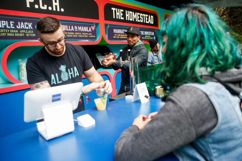 Brian Means, left, makes a Thrilla in Manila for Zoe Rountree, right, while Kevin Diedrich makes another drink at Cocktail Magic during the 10th annual Outside Lands Festival in Golden Gate Park in San Francisco on Friday, August 11, 2017. Photo: Nicole Boliaux, The Chronicle