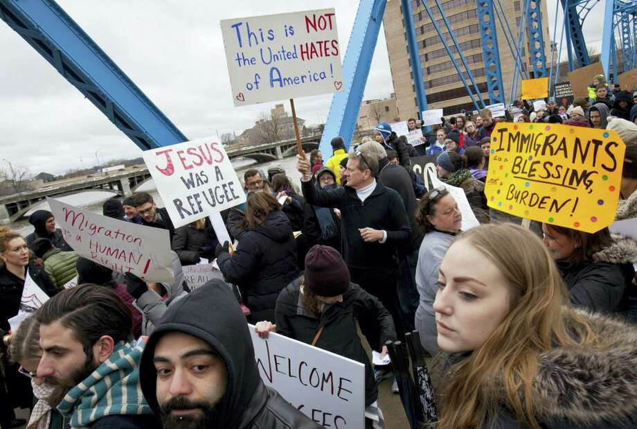 """Activists take part in the """"Bridges Not Walls Protest"""" at the Blue Bridge in downtown Grand Rapids, Mich., on Thursday. Photo: Cory Morse — The Grand Rapids Press Via AP  / The Grand Rapids Press"""