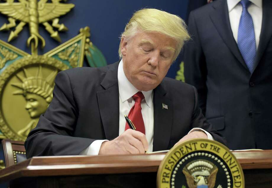 President Donald Trump signs an executive order on extreme vetting during an event at the Pentagon in Washington Friday. Photo: Susan Walsh — The Associated Press  / Copyright 2017 The Associated Press. All rights reserved.