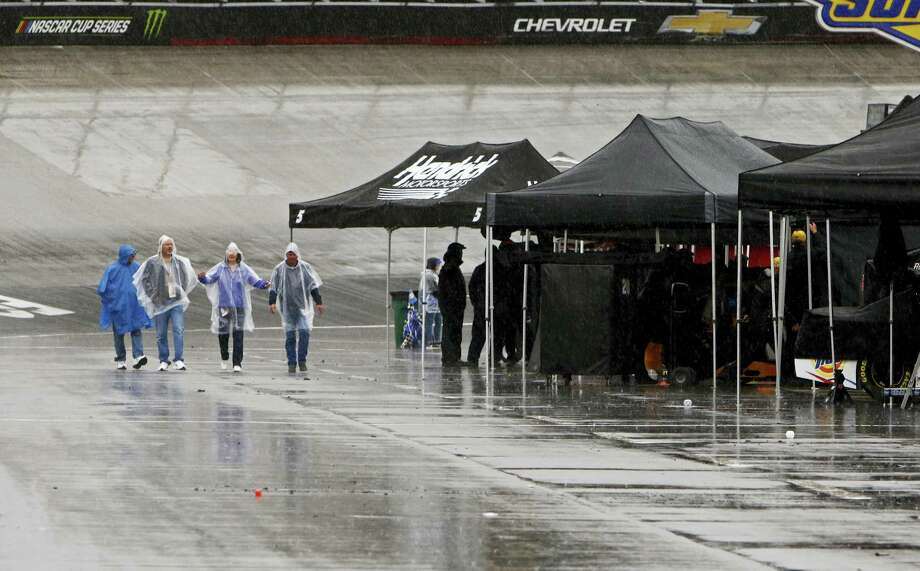 Fans walk down pit road in the rain on Sunday in Bristol, Tenn. Photo: Wade Payne — The Associated Press  / FR23601 AP