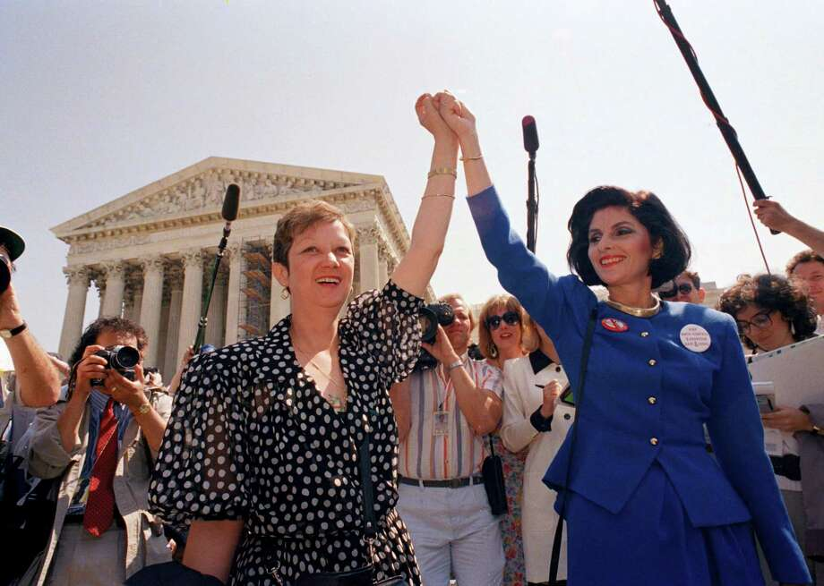 In this April 26, 1989 file photo, Norma McCorvey, Jane Roe in the 1973 court case, left, and her attorney Gloria Allred hold hands as they leave the Supreme Court building in Washington after sitting in while the court listened to arguments in a Missouri abortion case.   McCorvey died at an assisted living center in Katy, Texas on Saturday, Feb. 18, 2017, said journalist Joshua Prager, who is working on a book about McCorvey and was with her and her family when she died. He said she died of heart failure. Photo: AP Photo/J. Scott Applewhite, File   / Copyright 2017 The Associated Press. All rights reserved.