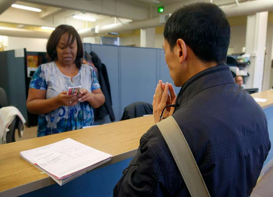 Associate Registrar Patricia Gant helps S.F. resident Simon Chan get a refund of mistakenly charged fees at CCSF. Photo: Paul Chinn, The Chronicle