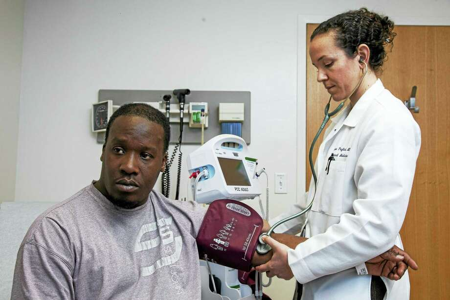 Dr. Lisa Puglisi checks the blood pressure of Adrian Heggie at the Yale New Haven Hospital — Primary Care Center Transitions Clinic, a program that provides health care to those released from prison. Photo: Derek Torrellas — Connecticut Health I-Team