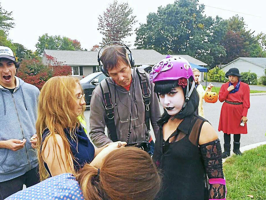 Cassidy Mosher and her costume crew make last-minute adjustments to Sophia Speringo as Soundman Kenneth White wires her for sound her as she's about to scooter down the street. Photo: Contributed Photo — Keith Bearden