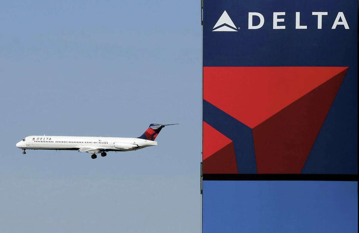 A Delta Airlines jet flies past the company's billboard at Citi Field, in New York.