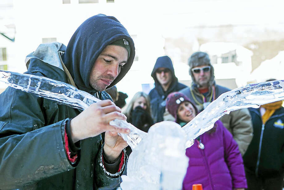Winter carnival guests watch an ice sculptor at work during last year's event. Photo: Contributed Photo