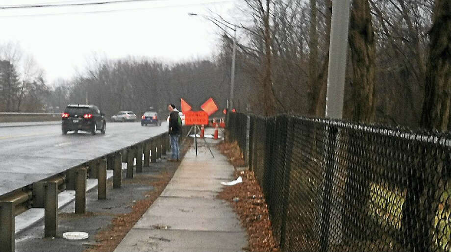 A morning pedestrian commuter confronts the closed sidewalk in the middle of the railroad bridge on Newfield Street, and then scrambles across the highway through traffic in order to proceed on his route. Photo: Jesse Torgerson Photo