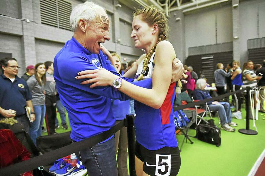Coginchaug senior Alex Alsup is congratulated by distance coach Jack McShane after Alsup came from behind to win the 1000 meter run in 3:00.44 at the Class S track and field championships Tuesday at the Floyd Little Athletic Center in New Haven. Alsup, seeded fifth with a time of 3:09.61 edged out Hale Ray sophomore Emily Sienna placing second in 3:02.42. Photo: Catherine Avalone - New Haven Register  / Catherine Avalone/New Haven Register
