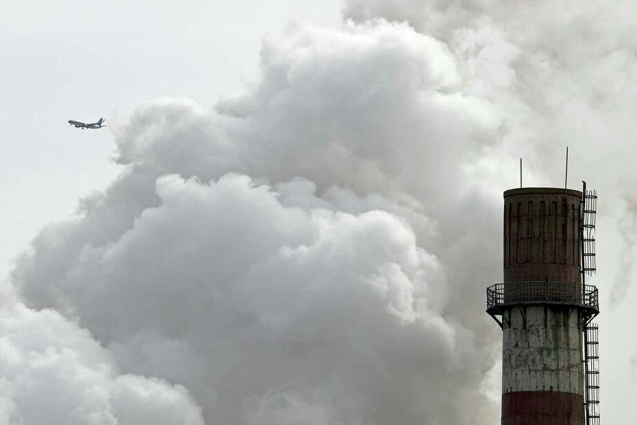 A passenger airliner flies past steam and white smoke emitted from China Huaneng Group's Beijing power plant that was the last coal-fired plant to shut down on March 18 the Chinese capital convert to clean energy like thermal power. Photo: AP Photo — Andy Wong, File  / Copyright 2017 The Associated Press. All rights reserved.