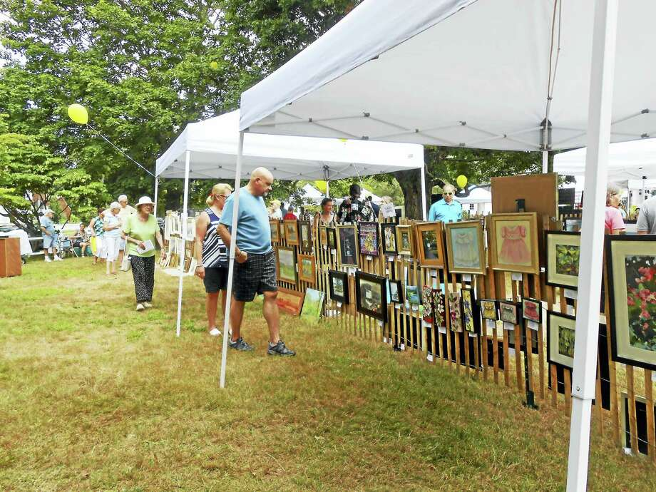 Guests peruse the Plein Air Painters Fence Show, set for July 29 in Old Lyme. Photo: Photos By Jane White