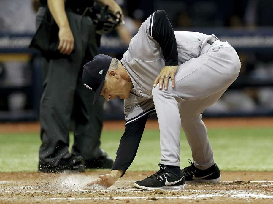 Yankees manager Joe Girardi covers home plate with dirt after being ejected along with pitching coach Larry Rothschild in the fifth inning Saturday. Photo: Chris O'Meara — The Associated Press  / Copyright 2017 The Associated Press. All rights reserved.