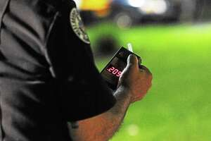 Photos by Tom Kelly IV A police officer reads a preliminary breath testing machine, which read over twice the legal limit after a test was given to a driver, who was subsequently arrested.  DUI Checkpoint was held on Friday May 17, 2013 on West Chester Pike near Five Points Road in West Goshen Township.  857 cars were contacted as they drove through the checkpoint, 12 drivers were field sobriety tested by officers, three people were arrested for DUI, one was arrested for drug possession, and 10 other traffic citations were issued that night, according to Sgt. Justin DiMedio of the West Goshen Police Department, Traffic Safety Division.