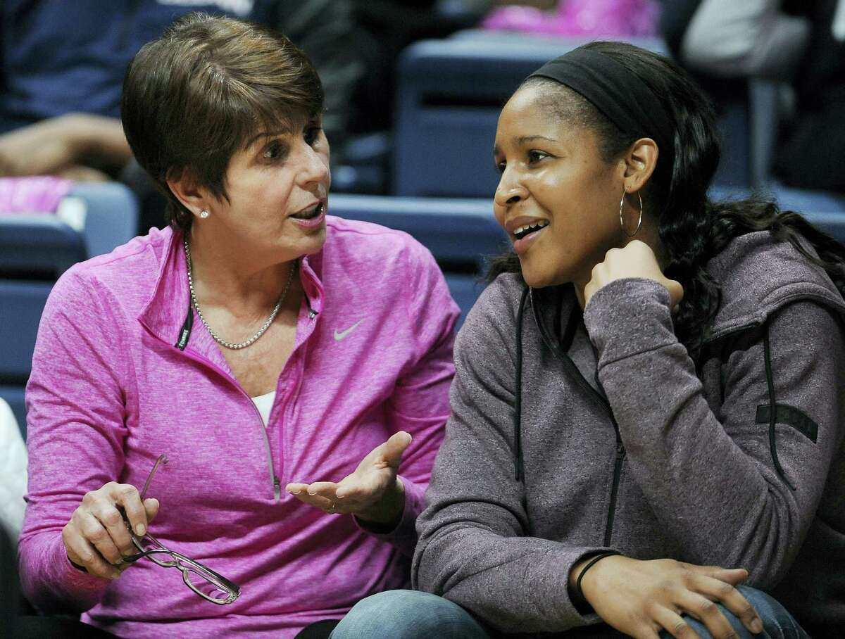 Minnesota Lynx and UConn alumni Maya Moore sits with Geno Auriemma's wife Kathy, left, in the second half of Saturday's game in Storrs.