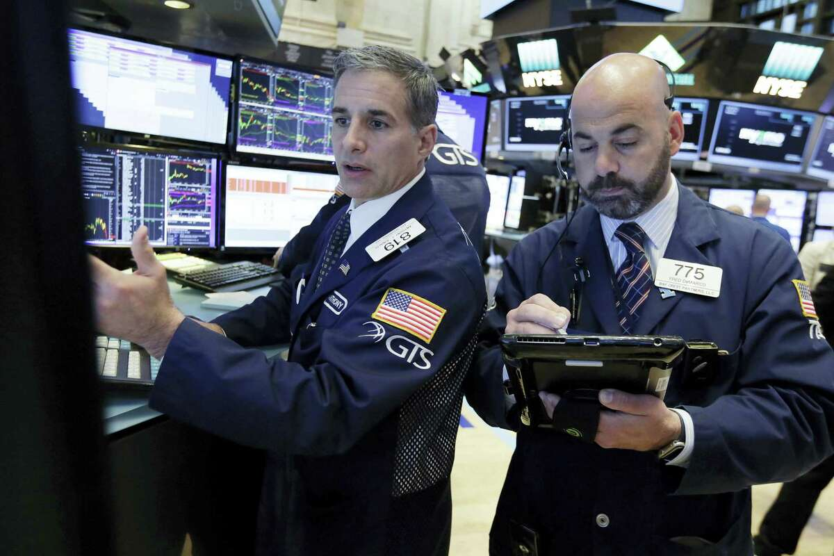 Specialist Anthony Rinaldi, left, and trader Fred Demarco work on the floor of the New York Stock Exchange Wednesday.