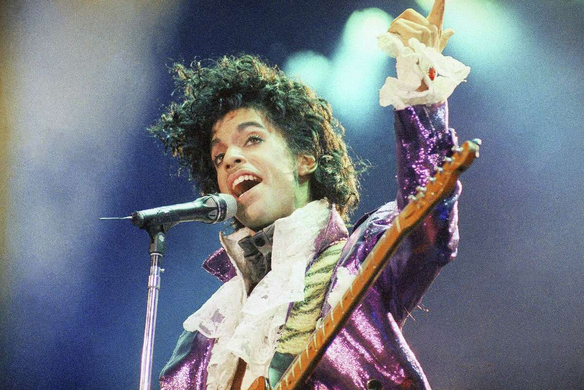 """In this Feb. 18, 1985 photo, Prince performs at the Forum in Inglewood, Calif. A year after Prince died of an accidental drug overdose, his Paisley Park studio complex and home is now a museum and concert venue. Fans can now stream most of his classic albums, and a remastered """"Purple Rain"""" album is due out in June 2017 along with two albums of unreleased music and two concert films from his vault."""
