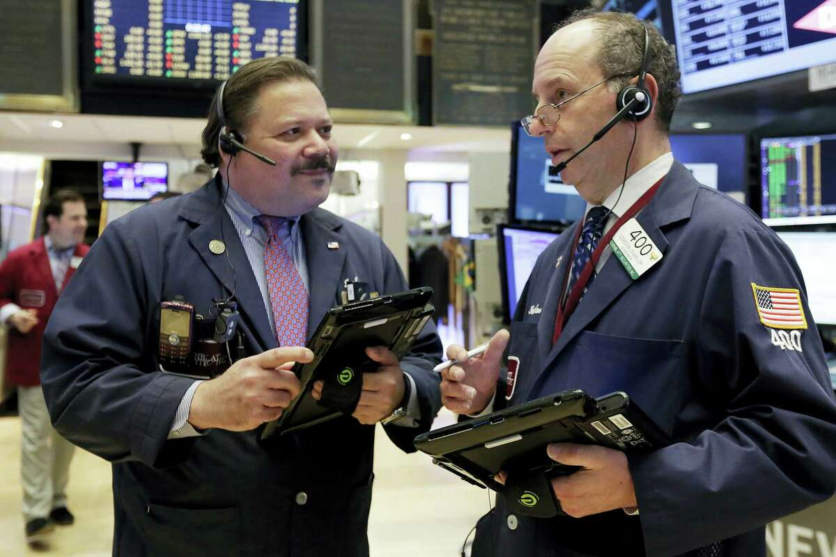 Traders John Santiago, left, and Gordon Charlop confer on the floor of the New York Stock Exchange, Monday. Technology and consumer-focused stocks are leading indexes slightly higher in early trading as investors return from a long holiday weekend.