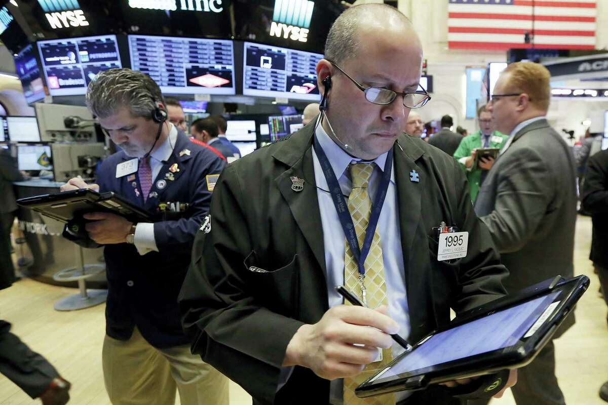 Trader Jeffrey Vazquez, foreground, works on the floor of the New York Stock Exchange, Monday. Technology and consumer-focused stocks are leading indexes slightly higher in early trading as investors return from a long holiday weekend.