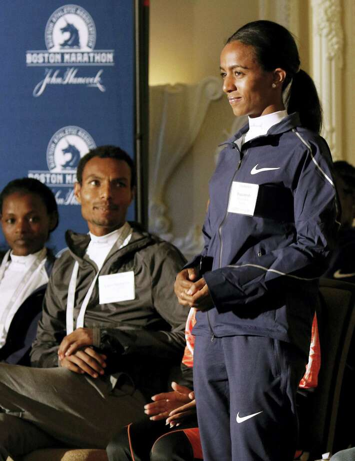 Top-seeded distance runners Atsede Baysa, left, and Lemi Berhanu Hayle, center, watch Buzunesh Deba during a Boston Marathon media availability Friday. Photo: Bill Sikes — The Associated Press  / Copyright 2017 The Associated Press. All rights reserved.